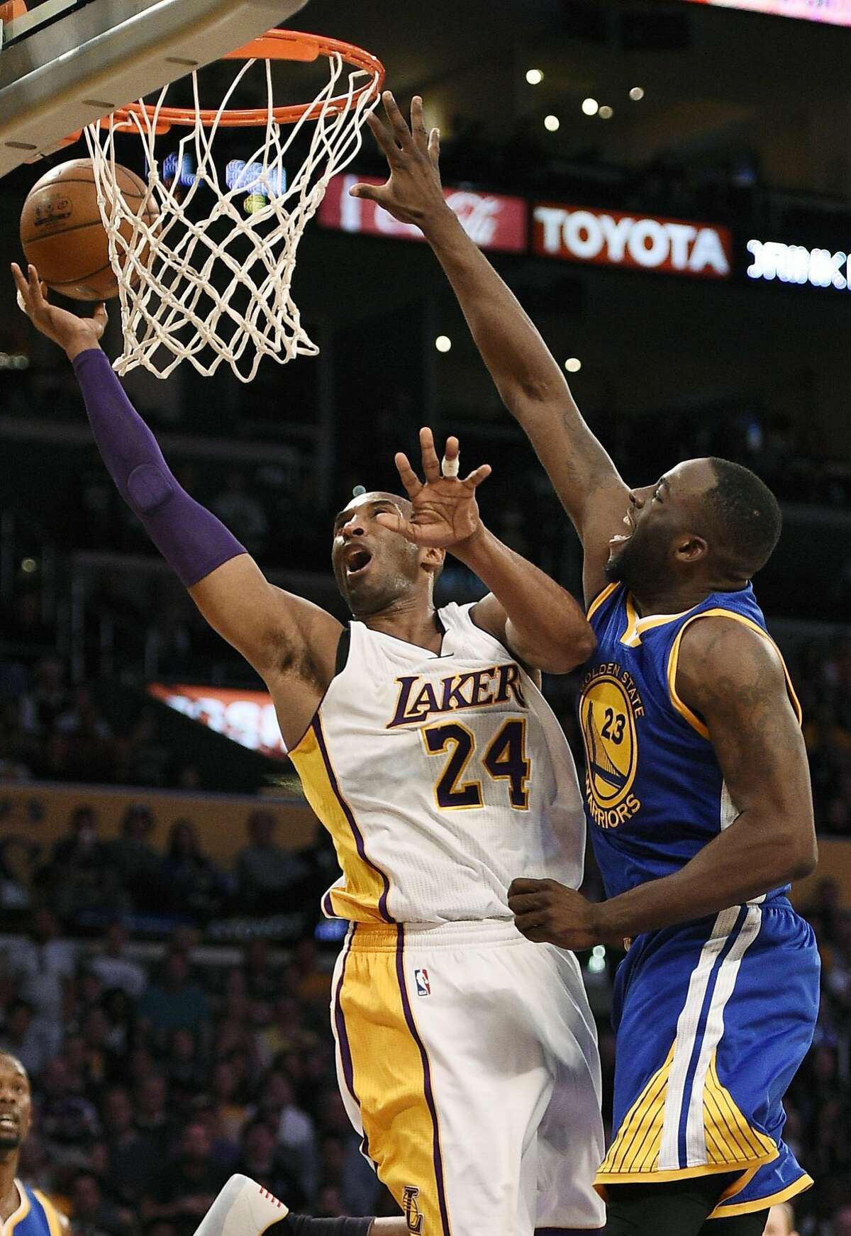 Los Angeles Lakers forward Kobe Bryant, left, attempts a shot while Golden State Warriors forward Draymond Green, right, defends during the first half of an NBA basketball game in Los Angeles, Sunday, March 6, 2016.