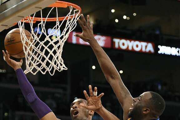 Los Angeles Lakers forward Kobe Bryant, left, attempts a shot while Golden State Warriors forward Draymond Green, right, defends during the first half of an NBA basketball game in Los Angeles, Sunday, March 6, 2016. (AP Photo/Kelvin Kuo)