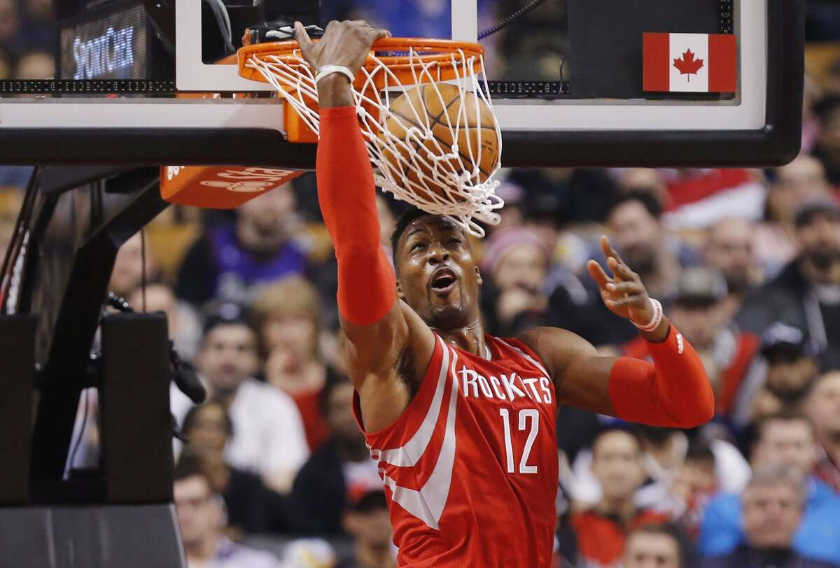 Houston Rockets' Dwight Howard (12) dunks on the Toronto Raptors during first half NBA basketball action in Toronto on Sunday, March 6, 2016. (Mark Blinch/The Canadian Press via AP) MANDATORY CREDIT