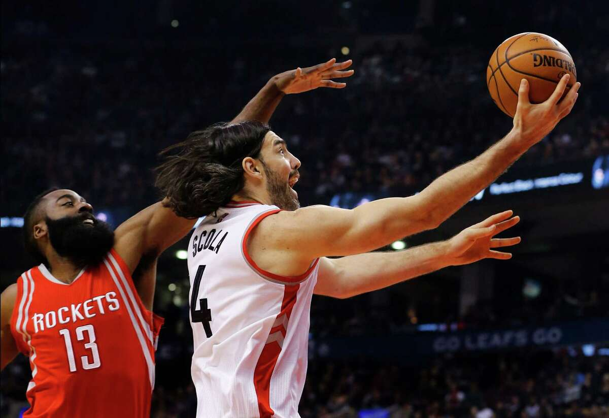 Toronto Raptors' Luis Scola (4) drives for the basket as Houston Rockets' James Harden (13) defends during first half NBA basketball action in Toronto on Sunday, March 6, 2016. (Mark Blinch/The Canadian Press via AP) MANDATORY CREDIT