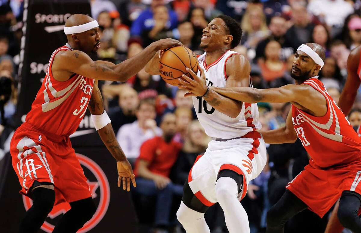 Toronto Raptors' DeMar DeRozan, centre, battles for the ball with Houston Rockets' Corey Brewer, right, and Jason Terry during second half NBA basketball action, in Toronto on Sunday, March 6, 2016.