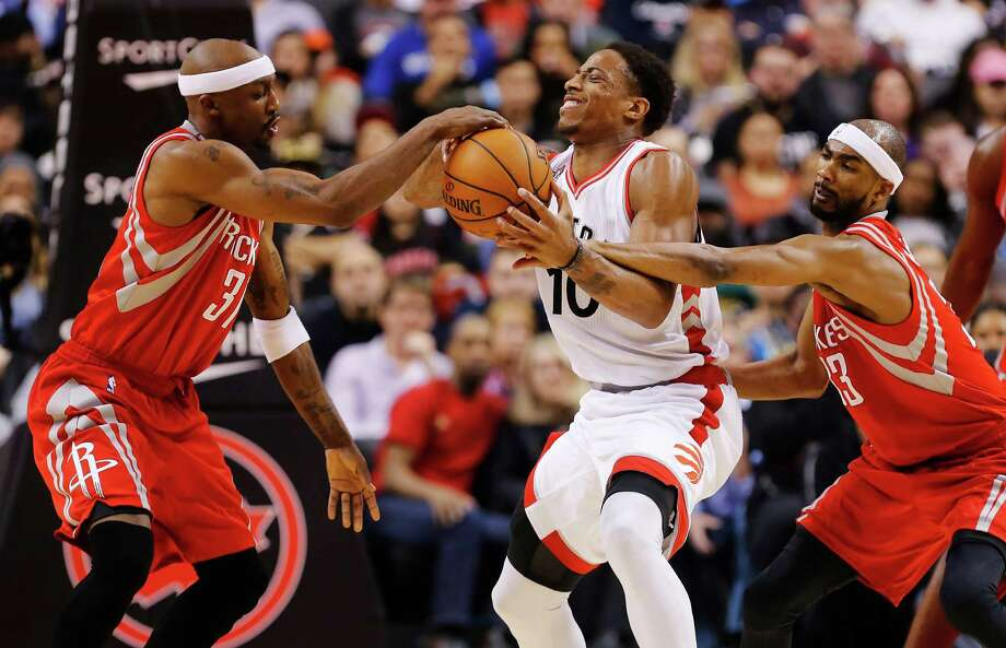 Toronto Raptors' DeMar DeRozan, centre, battles for the ball with Houston Rockets' Corey Brewer, right, and Jason Terry during second half NBA basketball action, in Toronto on Sunday, March 6, 2016. Photo: Mark Blinch, AP / CP
