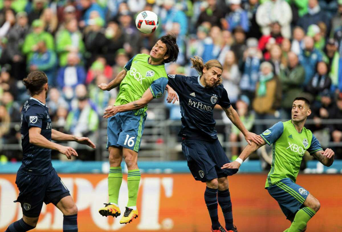 Seattle Sounders FC forward Nelson Valdez (16) heads the ball away from Sporting Kansas City'sChance Myers (7) in the first half of the team's MLS season opener versus Sporting Kansas City on March 6, 2016 at CenturyLink Field.