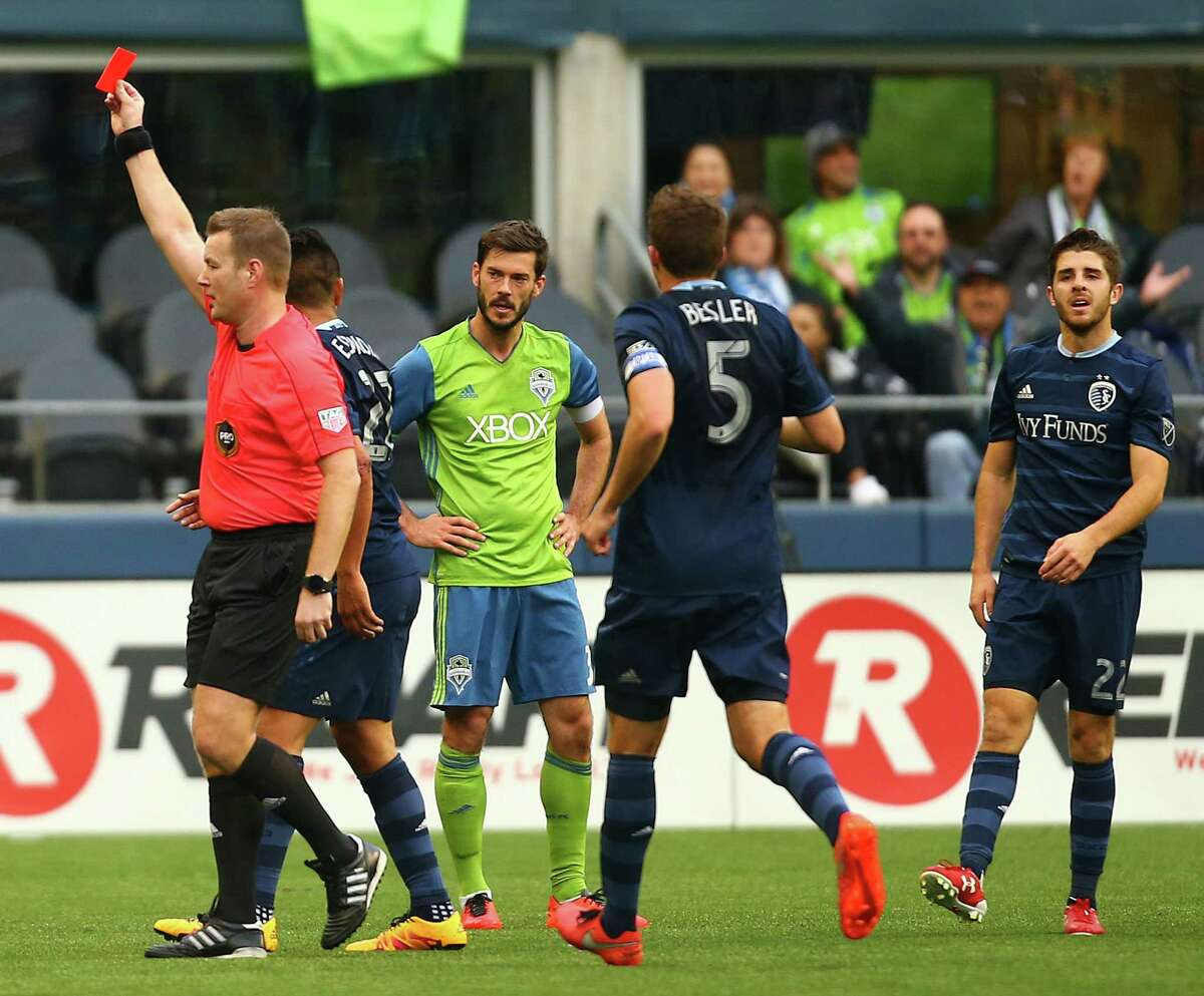 Referee Alan Kelly shows a red card to Seattle Sounders defender Oniel Fisher (off camera) as teammate Brad Evans looks on in disgust during the team's MLS opener versus Sporting Kansas City on March 6, 2016 at CenturyLink Field. The Sounders played a man down the rest of the game.
