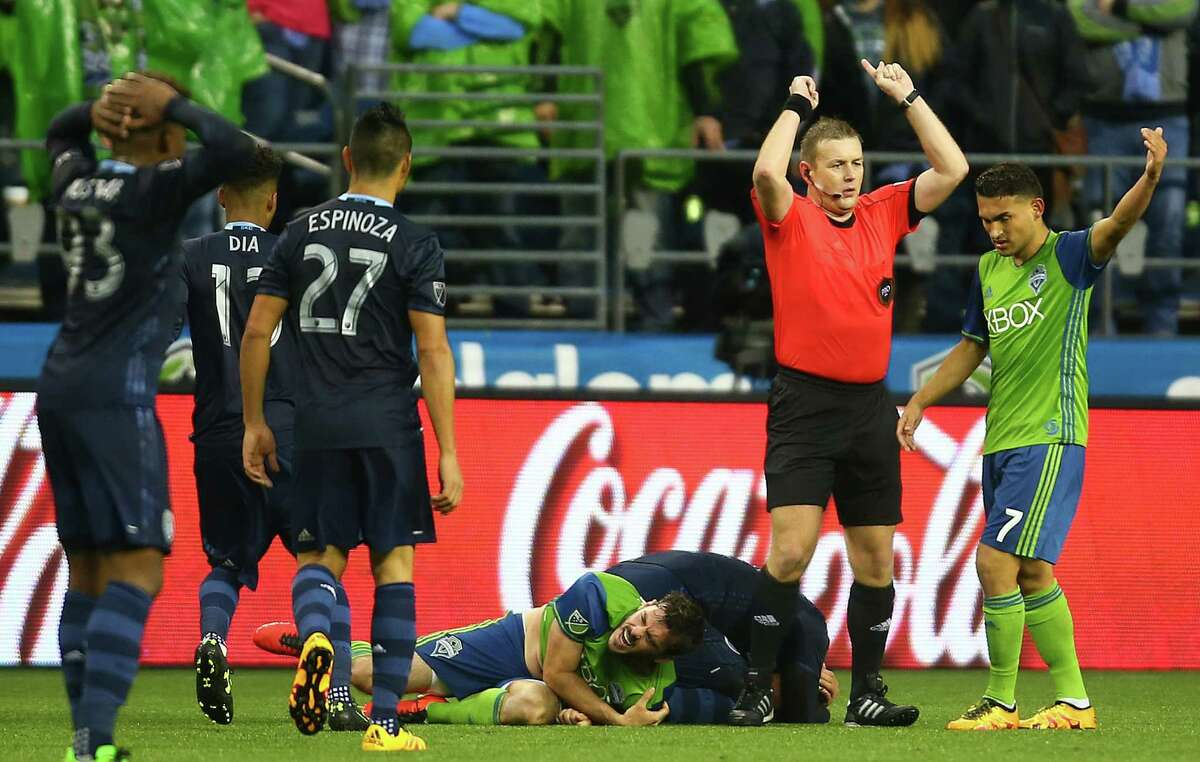 Seattle's Brad Evans (below) winces after falling hard on his shoulder as Cristian Roldan (7) calls over the medic in the second half of the Seattle Sounders' MLS season opener versus Sporting Kansas City on March 6, 2016 at CenturyLink Field. Sporting Kansas City won 1-0.