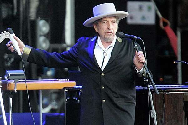 """FILE - This July 22, 2012 file photo shows U.S. singer-songwriter Bob Dylan performing on stage at """"Les Vieilles Charrues"""" Festival in Carhaix, western France.  The archives of Dylan have been acquired by the George Kaiser Family Foundation and the University of Tulsa and will be permanently housed in Tulsa. Kaiser Foundation director Ken Levit and university President Steadman Upham announced the acquisition Wednesday, March 2, 2016. (AP Photo/David Vincent, file) ORG XMIT: NY114"""