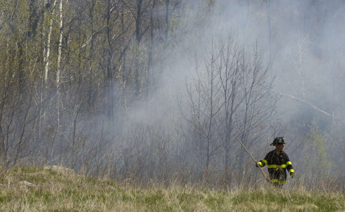 A Rensselaer city firefighter is seen at a brush fire in 2006. On Sept. 24, 2020 Warren County warned residents that there is a wildfire risk because of dry conditions. Times Union Staff Photo by Skip Dickstein -