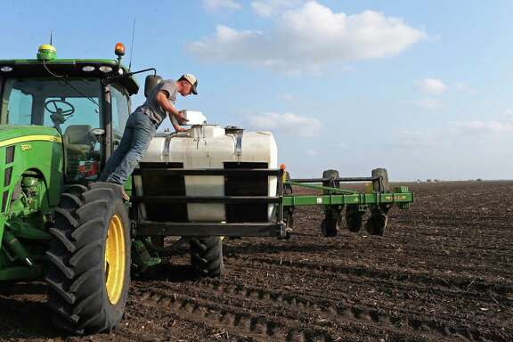 Kurt Rossow adds fungicide to fertilizer as he works a 120-acre field planting cotton southwest of Beeville, Texas, Wednesday, March 2, 2016. Texas leads the nation in production of cotton, which has plummeted in price as other nations step up production and stretchy manmade fibers enjoy a fashion moment reminiscent of the 1970s. Cotton growers are facing hard times and are hoping they can reclassify the product as an oilseed to make it eligible for subsidies that were lost in a trade dispute with Brazil.
