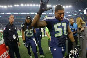 ARLINGTON, TX - NOVEMBER 01:   Bruce Irvin #51 of the Seattle Seahawks and  Richard Sherman #25 of the Seattle Seahawks walk off the field after beating the Dallas Cowboys 13-12 at AT&T Stadium on November 1, 2015 in Arlington, Texas.