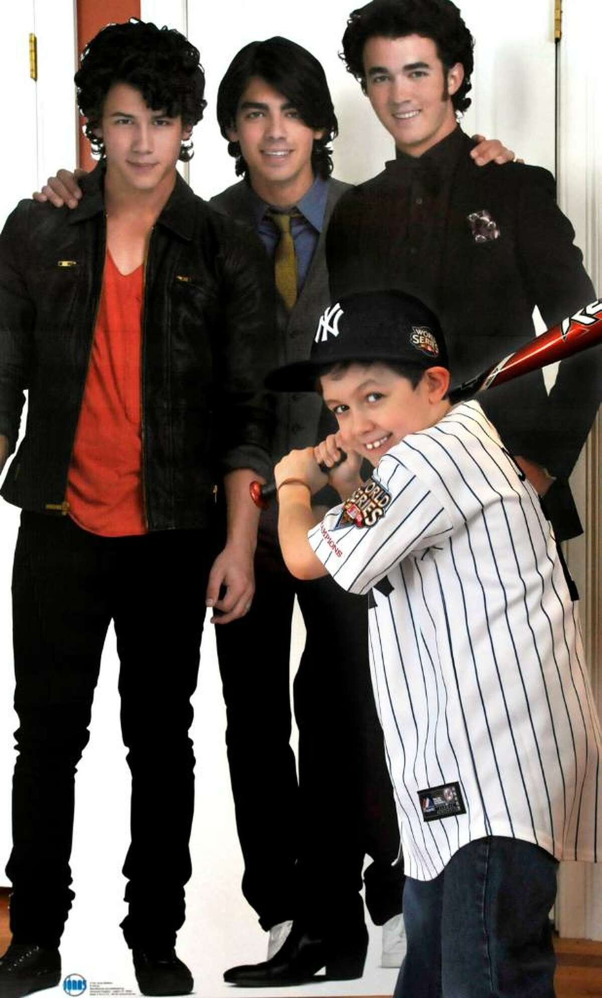 Caleb Schlissel, 6, in front of a cutout of the Jonas Brothers, in his Danbury home, on Friday, Feb.19,2010.