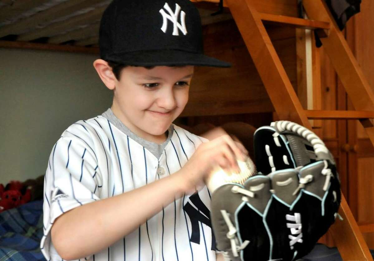Caleb Schlissel, 6, works his glove in preperation for baseball season, in the bedroom of his Danbury home, on Friday, Feb.19,2010.
