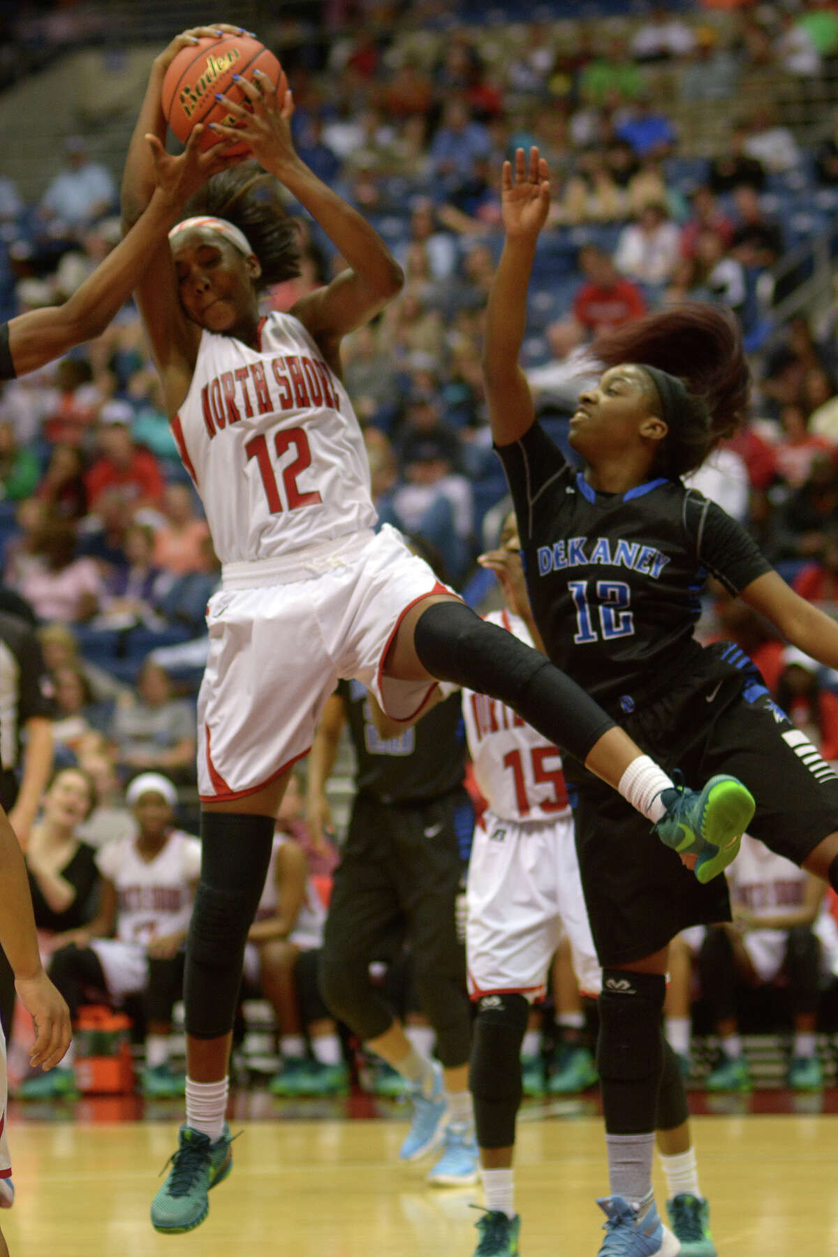 North Shore senior forward Alyssa Okoene (12) pulls a rebound down in front of Dekaney senior guard Kene Hamilton (12) during 1st quarter action of their Class 6A girls basketball state semifinal at the Alamodome in San Antonio on Friday, Mar. 4, 2016. (Photo by Jerry Baker/Freelance)