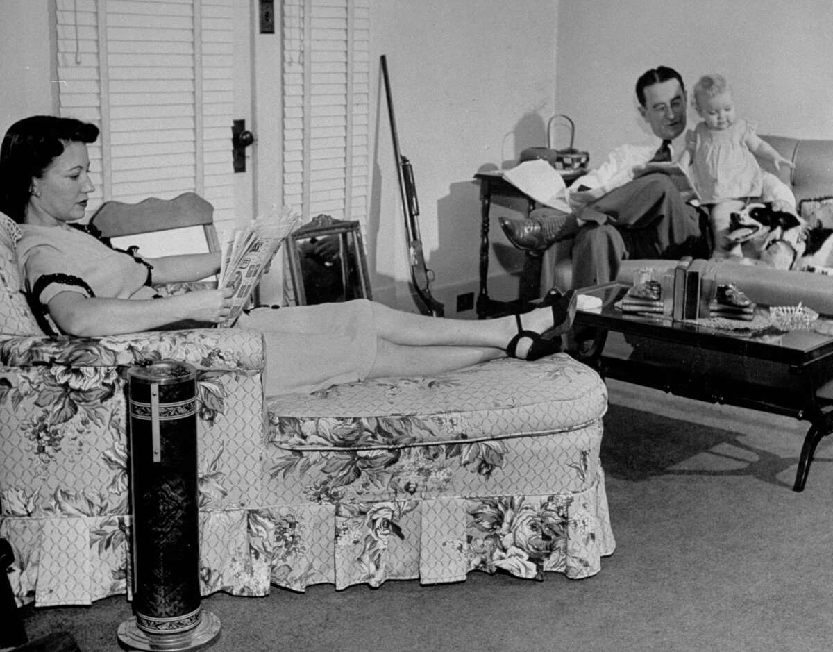May 1946: Mr. and Mrs. Edward McGill and daughter panicked by killer, sits in living room with shades drawn and shotgun by couch.