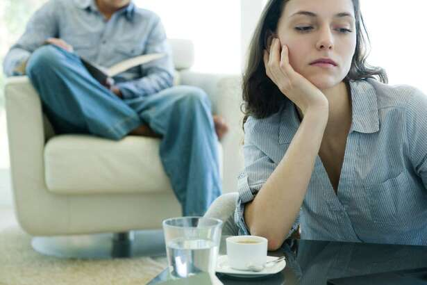 Woman leaning on elbow looking sad, man reading on sofa in background