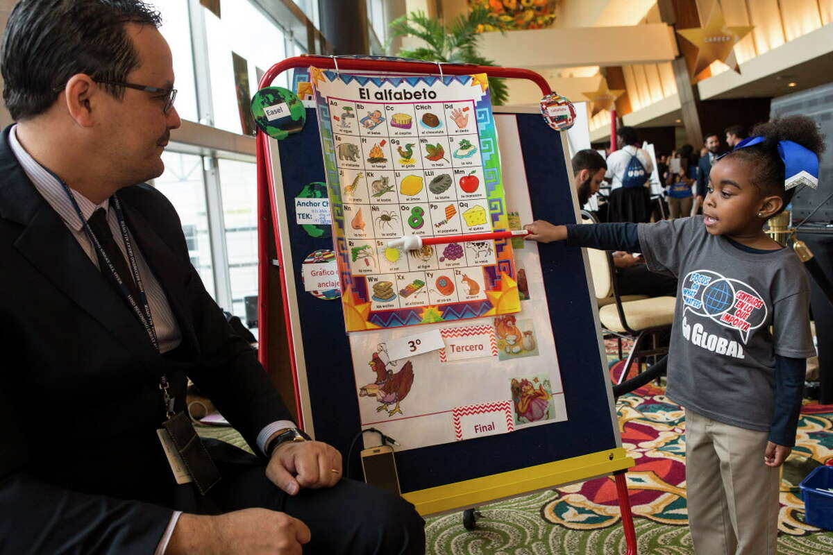 Victor Quintas, a Pre-K teacher at Mading Elementary, left, gives a dual language lesson demonstration with student Journee Pete outside the Houston Independent School District's State of The Schools event on Thursday, March 3, 2016, in Houston.