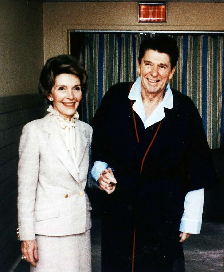 **FILE PHOTO** First lady Nancy Reagan stands with her husband, President Ronald Reagan, as he recuperates in a Washington hospital from an attempted assassination by John Hinckley in this April 1981 White House photo. Nancy Reagan died March 6, 2016, in Los Angeles. She was 94.  (Michael Evans/The White House via The New York Times) **EDITORIAL USE ONLY**