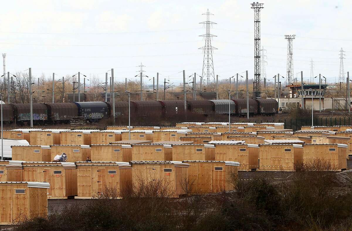Wooden sheds built by Doctors Without Borders are lined up in a new migrants camp in Grande Synthe, outside Dunkirk, northern France, Monday, March 7, 2016. About 150 migrants have abandoned the squalid, mud-filled Grande Synthe camp to move into wooden sheds with access to showers and other facilities. (AP Photo/Michel Spingler)