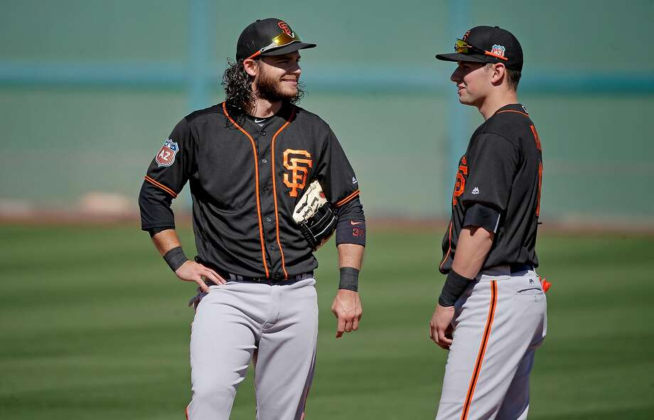 Brandon Crawford (left, with infield mate Joe Panik) is easing into spring training because of shoulder tendinitis. He is scheduled to make his defensive debut Wednesday or Thursday. Photo: Michael Macor, The Chronicle