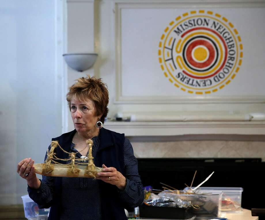 Jennifer Ewing demonstateholds a miniature boat while explaining the artistic ideas behind its creation to a group of artists at the Mission Neighborhood Center. Photo: Connor Radnovich Connor Radnovich, The Chronicle