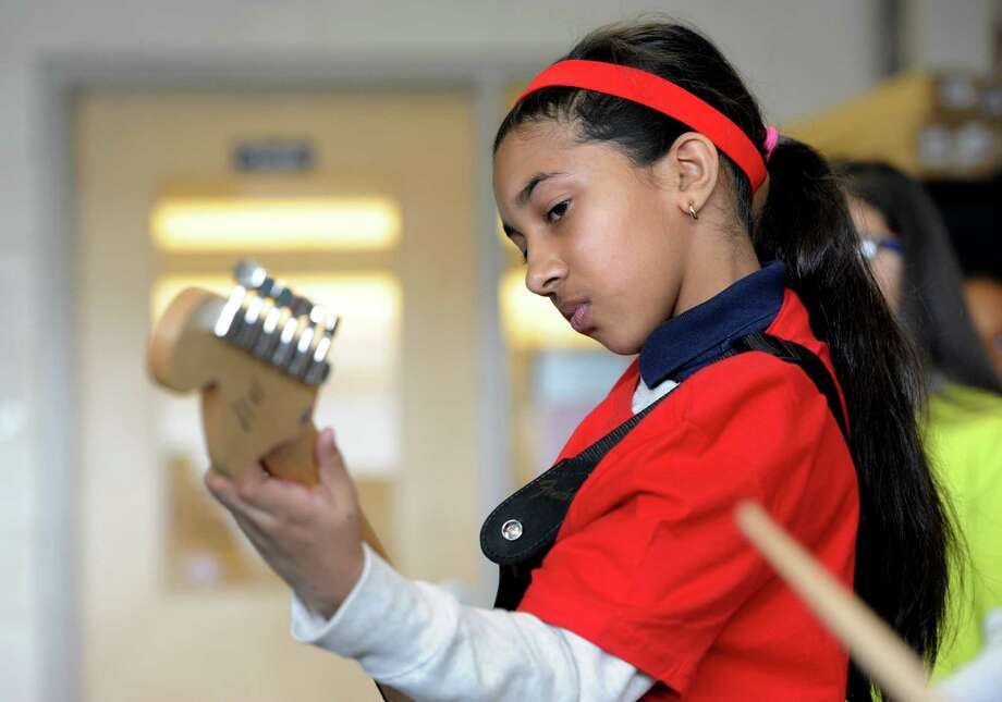 Tisdale School student Lindsey Mohammed plays a little guitar with musician and former New York Yankee, Bernie Williams plays guitar at the school in Bridgeport, Conn. on Monday, March 7, 2016.  Williams mentors the students as part of the national Turnaround Arts program that empowers high-need schools with arts resources, training and arts integration into other subject areas. Photo: Cathy Zuraw / Hearst Connecticut Media / Connecticut Post