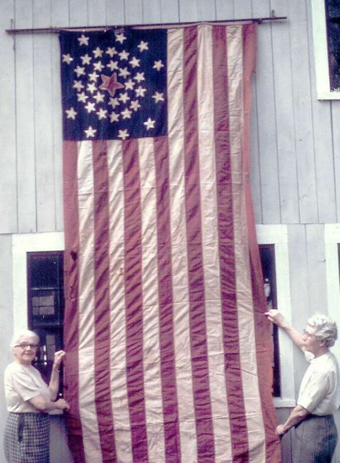 This photo taken in 1968 shows Harriet Hawley, left, and Mildred Terrill, displaying a Copperhead flag made during the civil war by Brookfield women living in the Obtuse district of the community.  On Wednesday evening, April 14, 2010, the Brookfield Historical Society will unveil, at their Museum, located at the intersection of Routes 25 and 133 in Brookfield Center, this rarely seen flag, which had been newly restored and will be on permanent display for the public to view.  It was sewn in 1861 by the female citizenry of Brookfield who were against the Union's participation in the Civil War. Following the unveiling, a presentation on the Copperhead movement in Connecticut will be given by Kathy Craughwell Varda,  of the Connecticut State Library. Admission is free and Photo: Contributed Photo / The News-Times Contributed