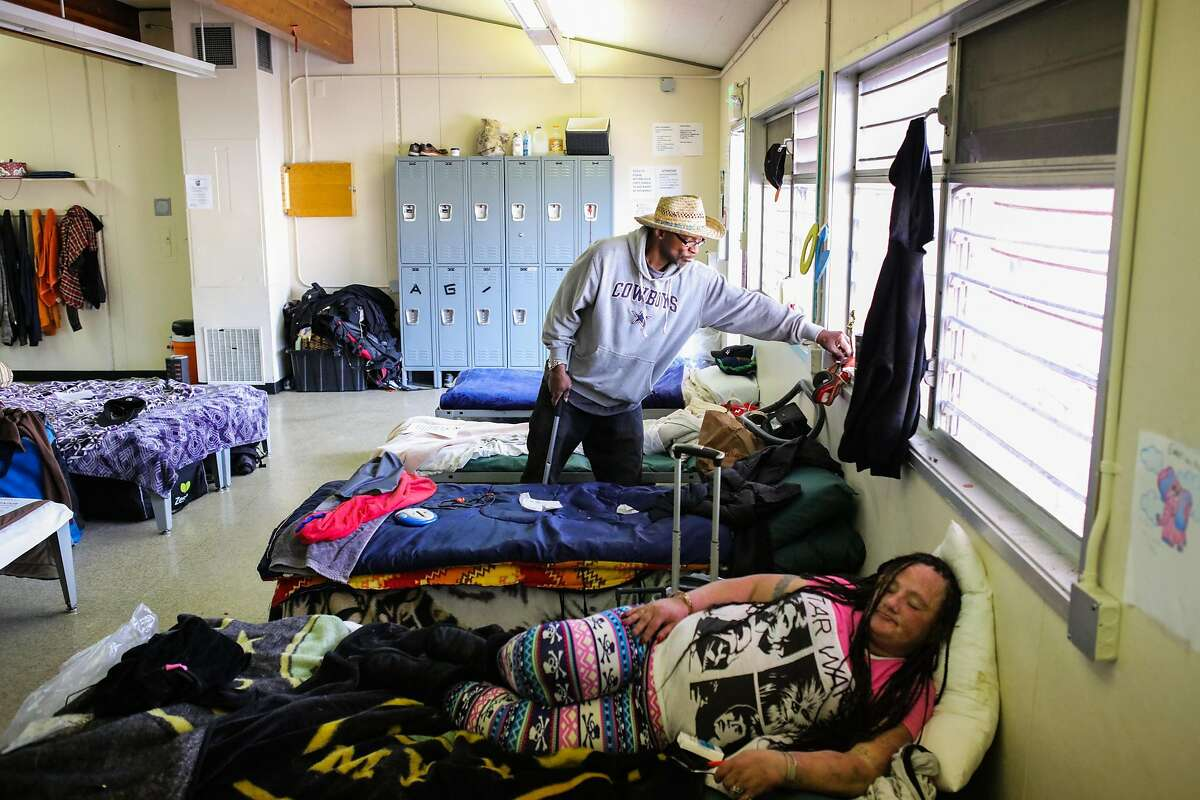Jonathan Payne folds organizes his area while Marin Santi relaxes on her bed, in their sleeping quarters at the Navigation Center on Monday, March 7, 2016 in San Francisco, California.