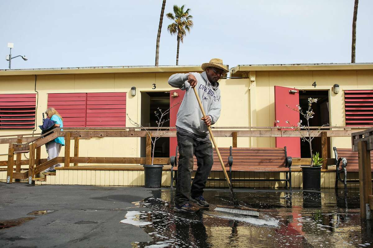 Jonathan Payne sweeps rain into a drain in the courtyard of the Navigation Center on Monday, March 7, 2016 in San Francisco, California.