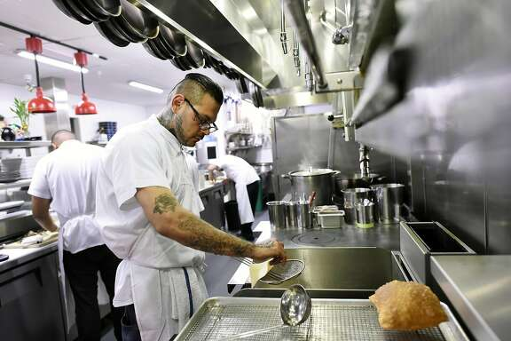 Edward Martinez, a former Fresno Bulldogs gang member who is now the executive pastry chef, deep fries dough for fry bread in the kitchen at Cadence restaurant in San Francisco, CA Wednesday, March 2, 2016.
