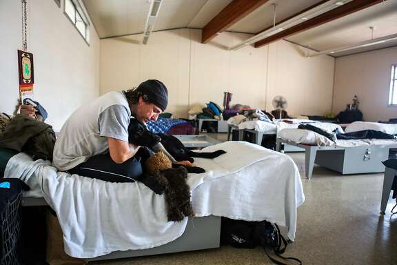 John Rao sits on his bed with dog Toby at the Navigation Center on Monday, March 7, 2016 in San Francisco, California.