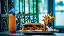 """The fried Shrimp Po Boy with fries  and """"Devilcat"""" cocktail at Bywater in Los Gatos, Calif. is seen on March 6th, 2016."""