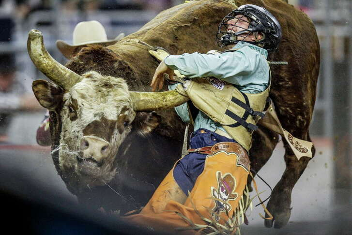 Bull rider Garrett Smith gets a horn under his protective vest after being bucked off during the Houston Livestock Show and Rodeo at NRG Stadium Saturday, March 5, 2016 in Houston.
