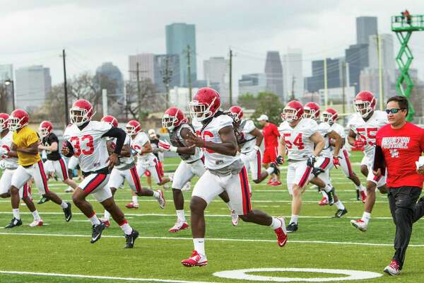 Houston football players run across the field while warming up during the Cougars' opening spring practice Monday, March 7, 2016, in Houston.