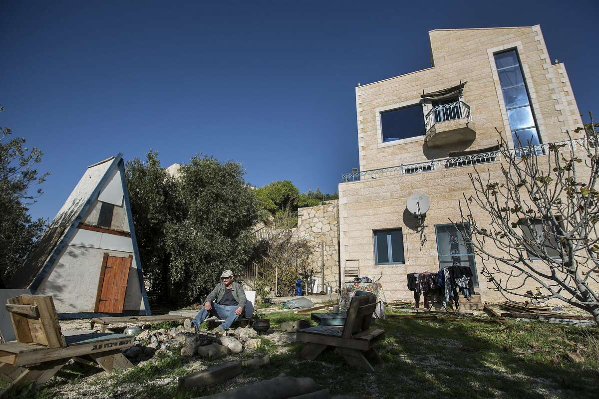 In this photo taken Sunday, Jan. 17, 2016, Moshe Gordon sits outside his guest house advertised on Airbnb international home-sharing site in Nofei Prat settlement at the West Bank. Palestinians say that by contributing to the settlement economy, Airbnb, like other companies doing business there, is perpetuating the expansion of Israel�s settlement enterprise. The criticism puts the travel site in the crosshairs of a burgeoning boycott movement and highlights the intricacies of the sharing economy in a legal anomaly such as the settlements, where residents are Israeli citizens but the land is occupied. (AP Photo/Tsafrir Abayov)