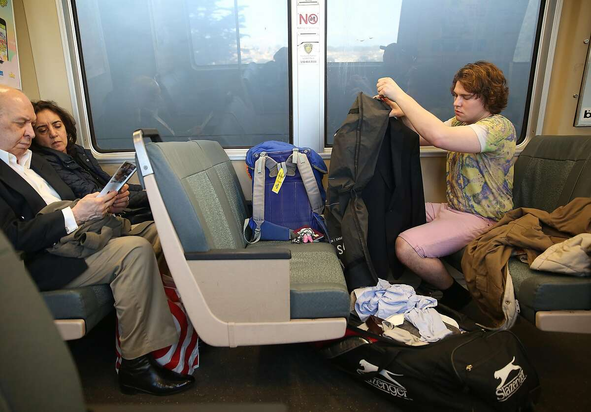 Leo May, 24 years old, from Quorn, England packs a suit as he heads to the airport on BART at the Daly City station on Monday, March 7, 2016.