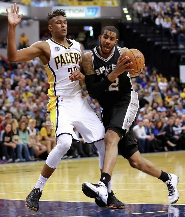 San Antonio Spurs forward LaMarcus Aldridge, right, collides with Indiana Pacers forward Myles Turner while driving to the basket in the second half of an NBA basketball game, Monday, March 7, 2016, in Indianapolis. Indiana won 99-91. (AP Photo/R Brent Smith)