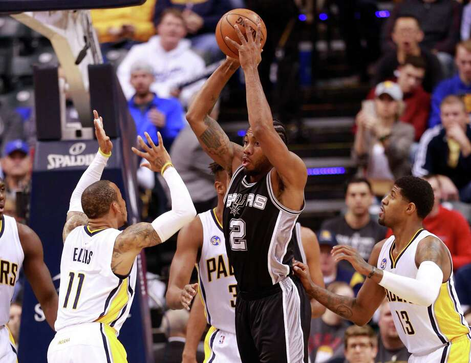 San Antonio Spurs forward Kawhi Leonard (2) passes the basketball between Indiana Pacers guard Monta Ellis (11) and Pacers forward Paul George (13) in the first half of an NBA basketball game, Monday, March 7, 2016, in Indianapolis. (AP Photo/R Brent Smith) Photo: R Brent Smith, FRE / AP / FR171017 AP