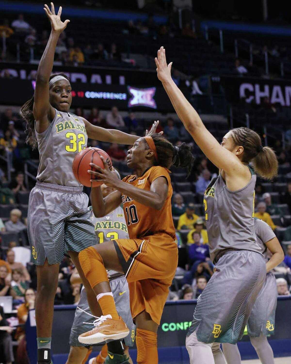 Texas' Lashann Higgs, center, tries to get past Baylor's Beatrice Mompremier (32) and Alexis Prince while on her way to the basket late in Monday night's game.