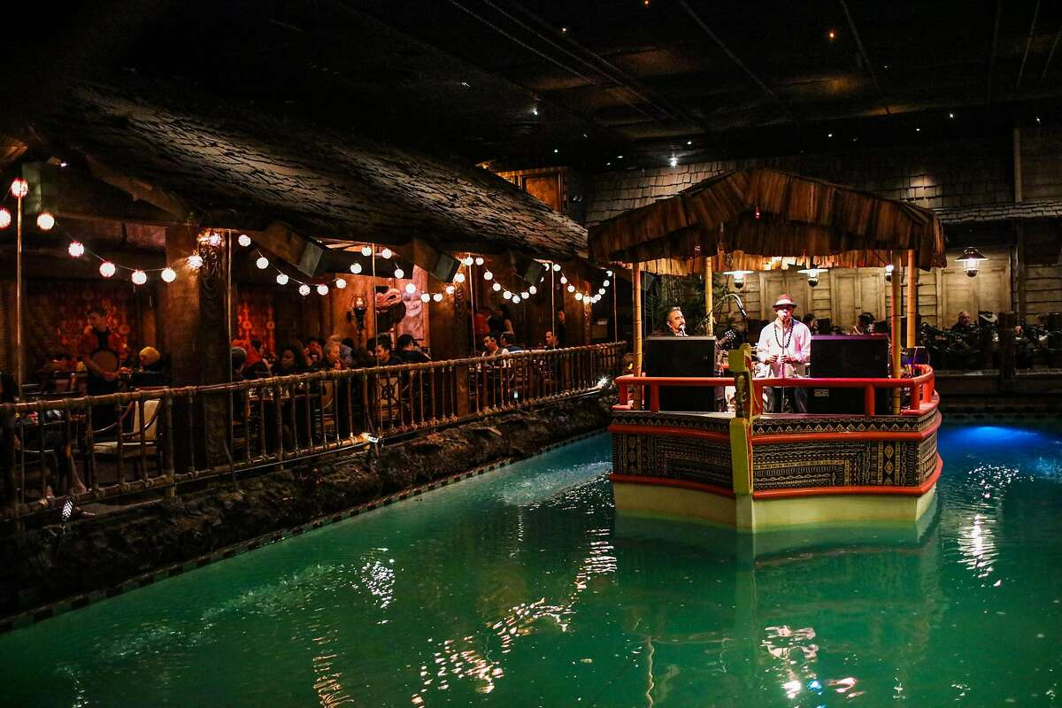 The Island Groove band plays on a boat in the middle of a pool at the Tonga Room.