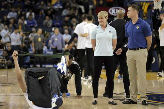 Chelsea Lane, head performance therapist for the Golden State Warriors, center, keeps an eye on Andrew Bogut (12) before the Golden State Warriors played the Orlando Magic at Oracle Arena in Oakland, Calif., on Monday, March 7, 2016.