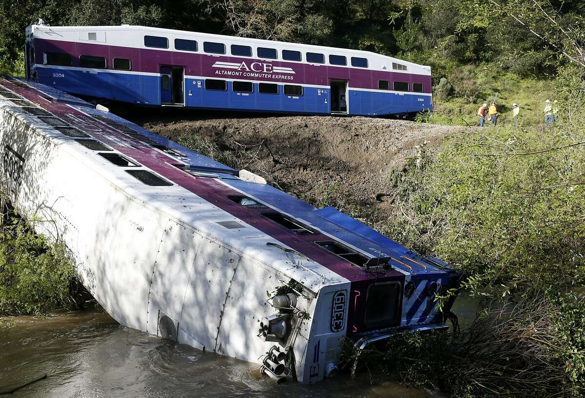 Union Pacific railroad officials inspect the track (upper right) while the lead car of an ACE commuter train lies on its side in Alameda Creek in Sunol, Calif. on Tuesday, March 8, 2016 after last night's derailment through Niles Canyon injured nine passengers.