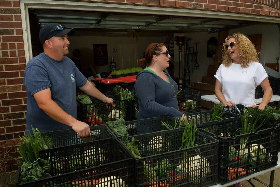 Kendall Kobza, right, picks up her weekly share of produce from Cypress Family to Farm Kitchen co-op founders Brandi and Jack McRill of Cypress. Photo: Jerry Baker, Freelance