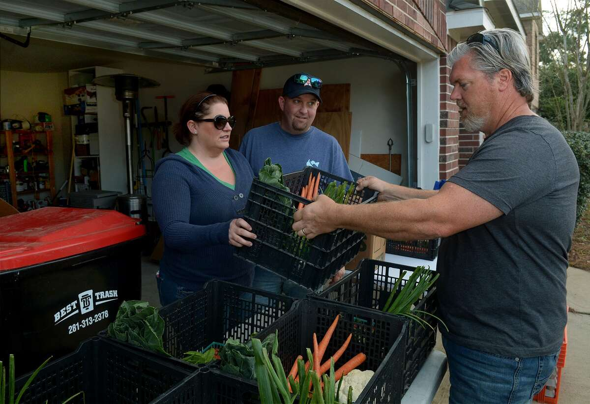Brandi McRill with her husband, Jack, hands out a produce