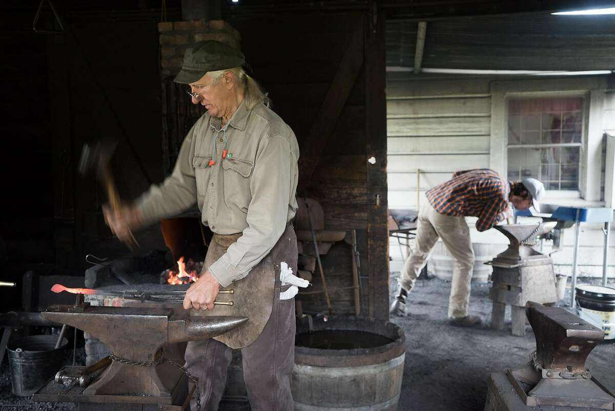 Mark Paul Kochan, left, and Brian Callen work in the blacksmith shop at the Marshall Gold Discovery State Historical Park.