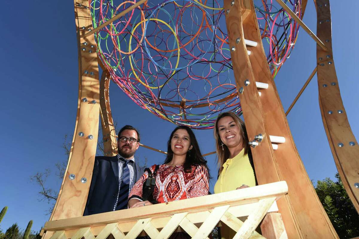 """Jeff Olivares, left, Belen Aguilar and Andrea Munoz of PBK Architects stand in the basket of their hot-air balloon structure inspired by Dr. Seuss' classic """"Oh! The Places You'll Go"""" at the San Antonio Botanical Garden, on Thursday, March 3, 2016."""