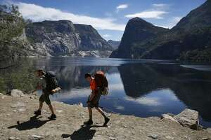Keith Arnold, left, and Ian Moore start off their weekend backpacking trip as they hike by Hetch Hetchy Reservoir June 12, 2015 in Yosemite National Park, Calif. The 117-billion-gallon reservoir supplies water to millions of Bay Area residents.
