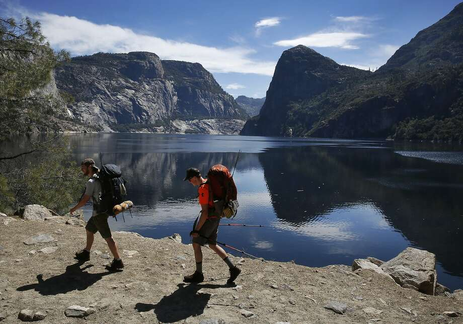 Keith Arnold, left, and Ian Moore start off their weekend backpacking trip as they hike by Hetch Hetchy Reservoir. Photo: Leah Millis, The Chronicle