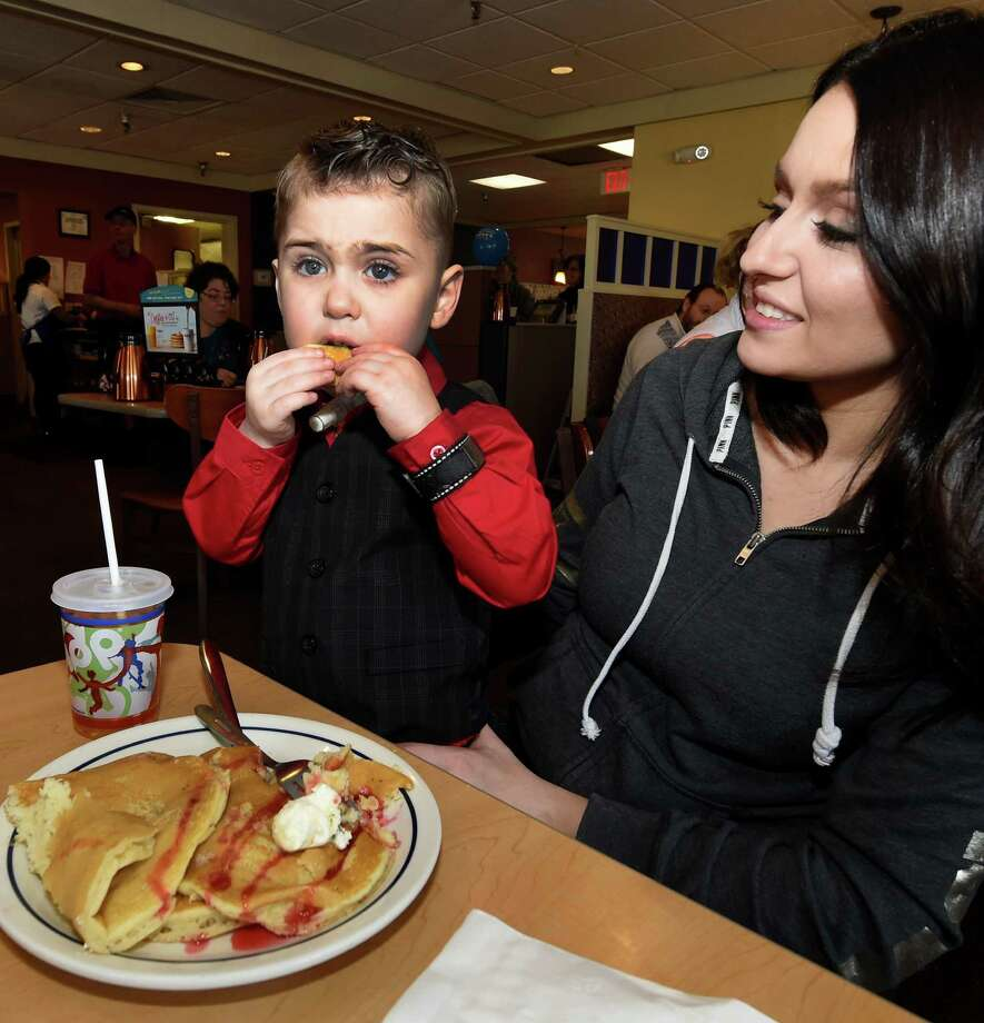 Children's Hospital at Albany Medical Center patient Keaton McGivney, 5, enjoys his pancakes on National Pancake Day at IHOP with his mother Teryn Lisicki Tuesday, March 8, 2016, in Clifton Park, N.Y. IHOP served free short stacks of pancakes for a donation to the Children's Hospital of the Albany Medical Center.  (Skip Dickstein/Times Union) Photo: SKIP DICKSTEIN / 10035739A