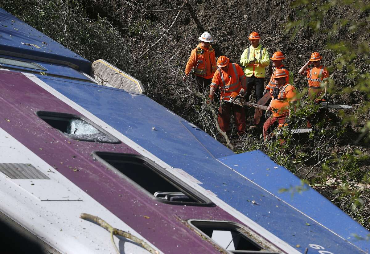 A Union Pacific crew removes foliage before they can remove two ACE Commuter train cars in Sunol, Calif. on Tuesday, March 8, 2016 after last night's derailment through Niles Canyon injured nine passengers.