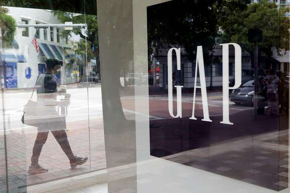 In this Saturday, Aug. 15, 2015, photo, a pedestrian walks past a Gap store in Miami. Gap reports earnings on Thursday, Feb. 25, 2016. (AP Photo/Lynne Sladky)