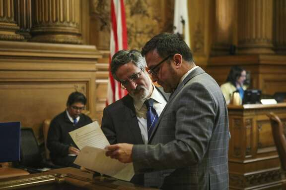Supervisor Aaron Peskin looks over paperwork with Supervisor David Campos, during a Board of Supervisors meeting at City Hall, in San Francisco, California on Tuesday, February 23, 2016.